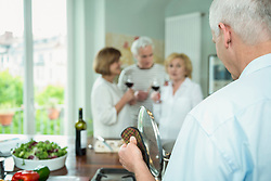 Mature man preparing food while friends drinking wine in background