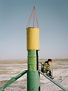 A young boy plays in a russian era playground near Bulgan town, Mongolia.<br /> <br /> Travels in the Gobi desert region.