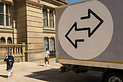 Two arrows on the side of a van pointing in different directions as people pass by on 15th June 2021 in Birmingham, United Kingdom. The scene is one of opposing direction, and differering ideas and opinions.