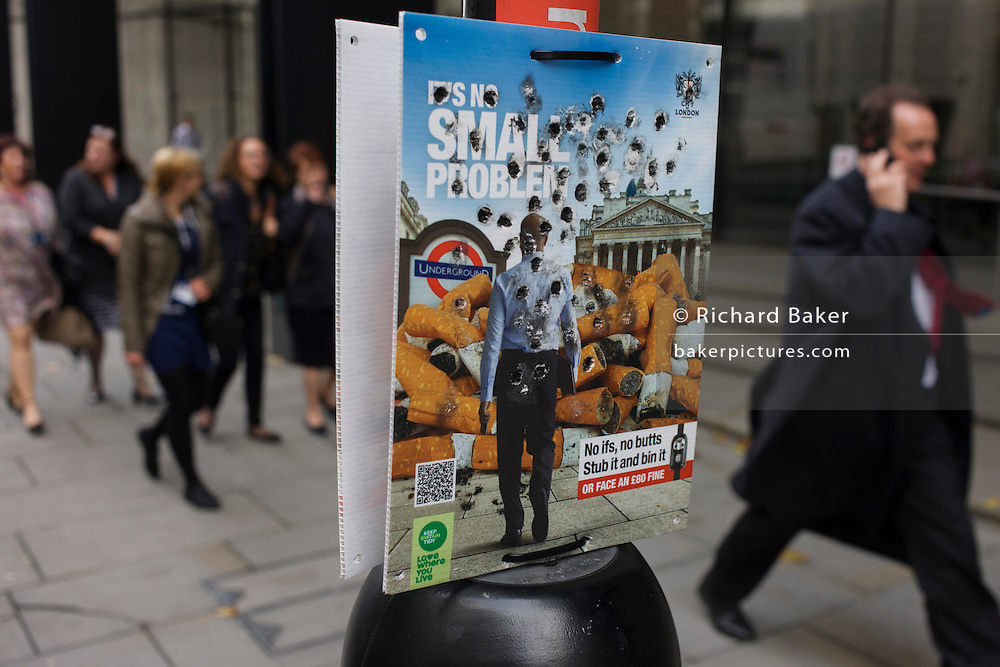 City of London (corporation) anti-butts litter campaign with burn holes from stubbed out cigarattes.