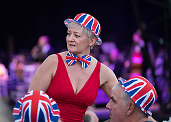 © Licensed to London News Pictures.22/08/15<br /> Castle Howard, North Yorkshire, UK. <br /> <br /> A woman in a Union Flag bowler hat talks to friends as she and hundreds of other people attend the 25th anniversary of the Castle Howard Proms event near York. The theme of the event this year is a commemoration of the 75th anniversary of the Battle of Britain and the 70th anniversary of VE day and brings an evening of classic musical favourites celebrating Britishness to the lawns of Castle Howard.<br /> <br /> Photo credit : Ian Forsyth/LNP