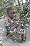 Africa, Tanzania, Lake Eyasi, Portrait of a young Hadza mother with her baby, A small tribe of hunter gatherers AKA Hadzabe Tribe August 2009