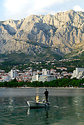 View from the sea of small boat and fisherman, with the Biokovo National Park, part of the Dinaric Alps, in the background. Makarska, Croatia