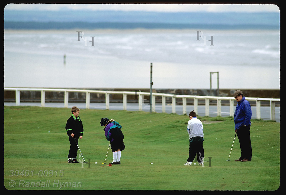 Kids practice on putting green with their dad near the famous Old Course at St. Andrews Links. Scotland