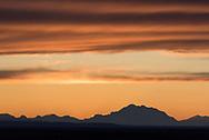 Sunset lights up the clouds above Mt. Denali as seen from Nenana, Alaska