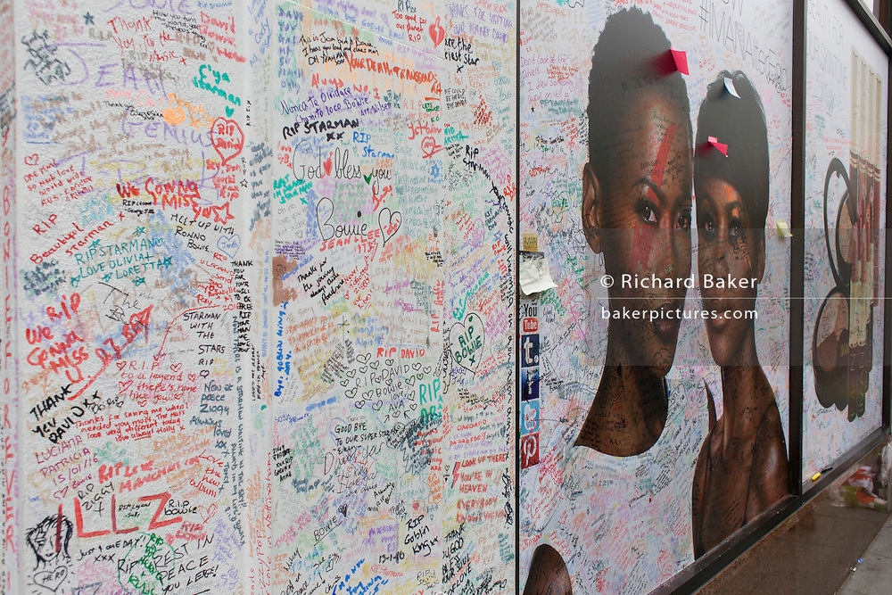 The growing shrine to musical artist David Bowie in Brixton, south London, the place of his birth in 1947. Bowie's wife, Iman, coincidentally hasher cosmetic products outside the Morleys department store, alongside her husband's makeshift memorial.