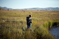Zack Little re-ties his fly while fishing with friends on opening day of Flat Creek on Saturday on the National Elk Refuge.