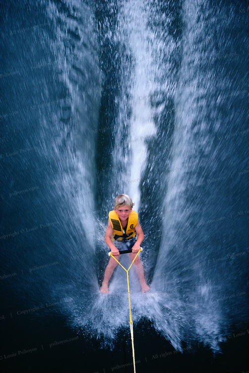 Patrick McCormick, age 6 kicks off his skis when he moving about 15 m.p.h. 24 kmh.  to barefoot ski in Cypress Gardens, Florida 1982