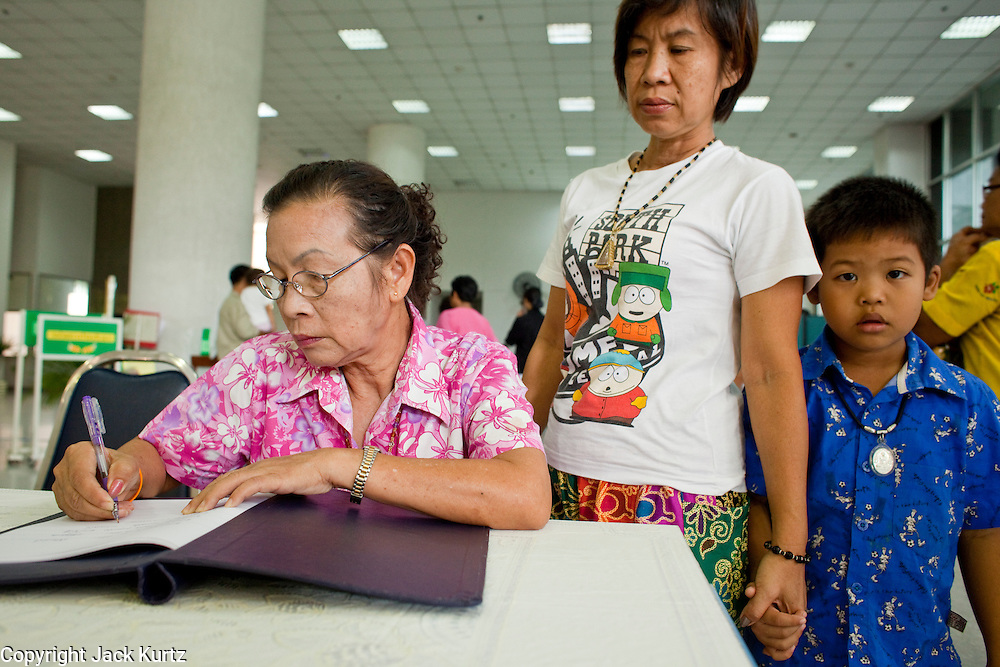 Sept. 22, 2009 -- BANGKOK, THAILAND: A family signs a get well note in the lobby of Siriraj Hospital for King Bhumibol Adulyadej, the 81-year-old King of Thailand. The King has been admitted to hospital suffering from a fever. Doctors at Siriraj Hospital said the world's longest-serving monarch, had shown signs of fatigue and was being treated with antibiotics. King Bhumibol is deeply revered by most Thais and his health is a matter of public anxiety. His Majesty was admitted on Saturday suffering from a fever, fatigue and loss of appetite. Doctors continued to treat the King with intravenous drips and antibiotics, hospital officials said. More than 3,500 people have come to the hospital to pray for the King's speedy recovery and to sign get well cards for him.  Photo by Jack Kurtz