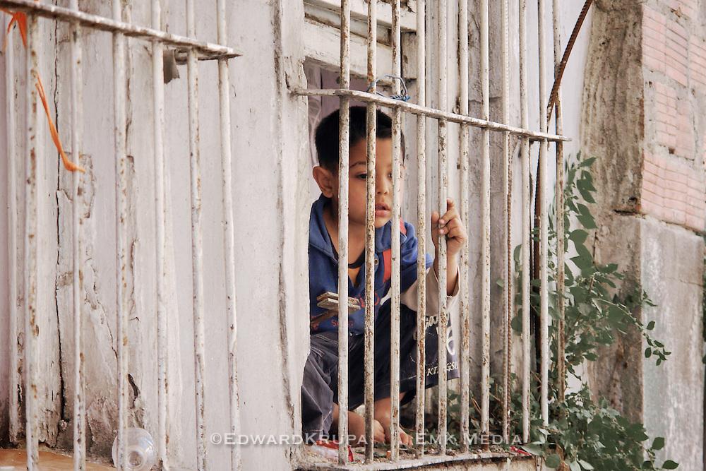 Boy looking outside his window in the Kurdish ghetto, Istanbul, Turkey.