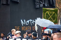 © Licensed to London News Pictures. 24/11/2018. LONDON, UK.  Graffiti reading 'Mother' is spray painted into The Women of World war II memorial by a man (partially seen wearing red hat) in Whitehall during a protest by Extinction Rebellion. He was quickly stopped by police and detained. The group is conducting a campaign of civil disobedience to highlight the urgency of action on climate change and species loss.  Photo credit: Cliff Hide/LNP