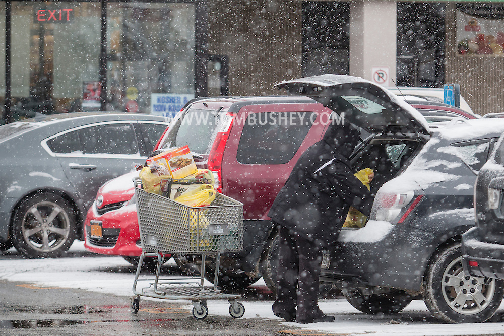 A person loads groceries into a car as snow falls in the ShopRite parking lot in Middletown, New York. People were buying food in advance of the blizzard forecast to hit Orange County.  The county declared a state of emergency later in the day.