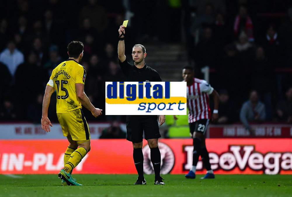 Football - 2018 / 2019 FA Cup - Third Round: Brentford vs. Oxford United<br /> <br /> Oxford United's John Mousinho is shown a yellow card by Referee Jeremy Simpson, at Griffin Park.<br /> <br /> COLORSPORT/ASHLEY WESTERN