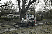 One on many unsung heroes from Hurricane Katrina, an independent contractor  scrapes teh sludge off street in Bat St. Louis so residents can return to their homes Friday Sept. 1,2005.(Photo/SuziAltman)