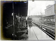 steam train arriving at station with rain water on rail track, flood Seine River Paris January 1910