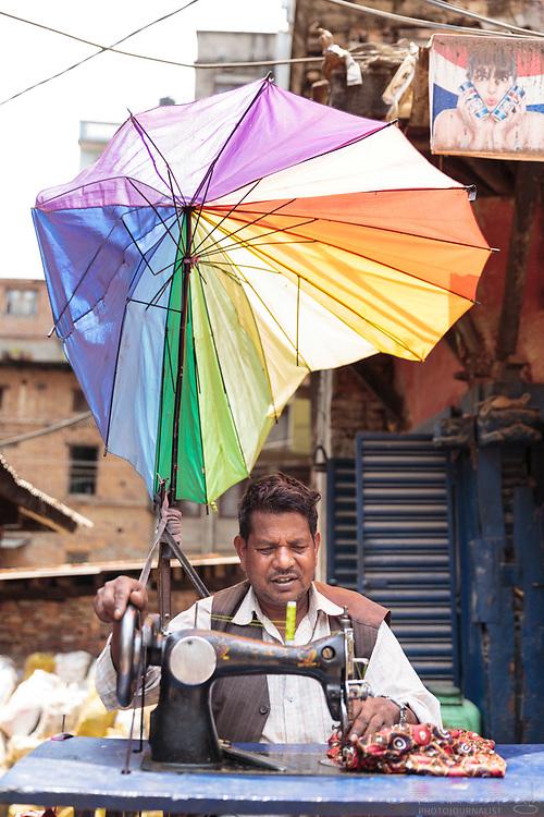 A man using a sewing machine n the street beneath a broken rainbow-coloured umbrella, Bhaktapur, Kathmandu Metropolitan City, Nepal