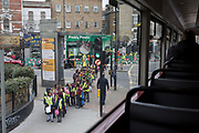 A group of Primary school age cross the road in Camberwell, Southwark, on 27th March 2019, in London, England