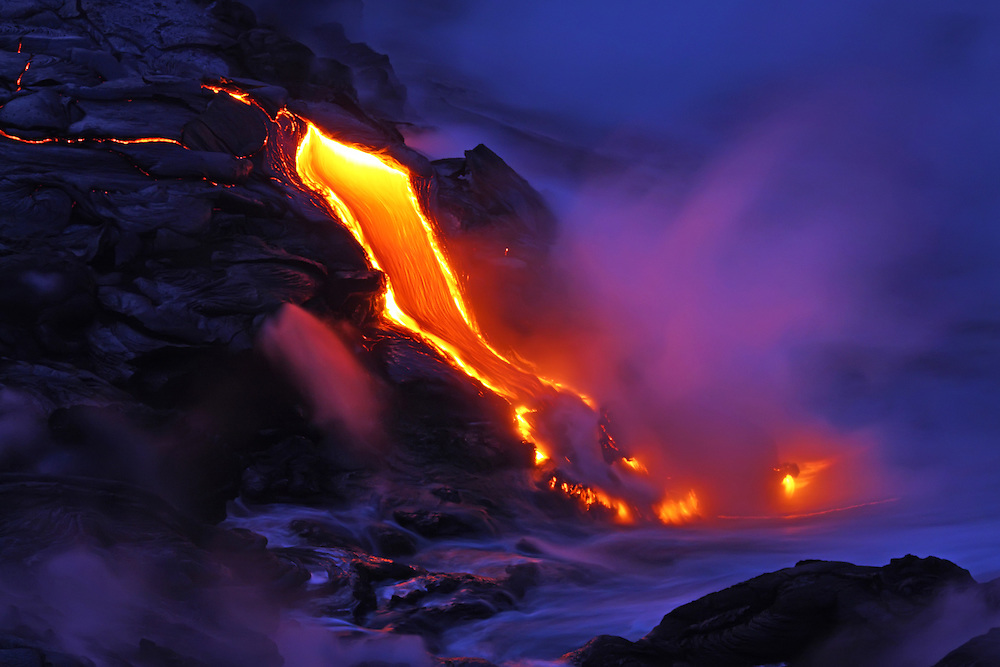 A finger of lava gracefully cascades into the sea at the Waikupanaha ocean entry, while its glow radiates warm pastel shades in the rising steam plume.