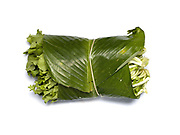 Pak kard, a green leafy vegetable (wrapped in a banana leaf) grown in the Tai Dam ethnic minority village of Ban Na Mor, Oudomxay province, Lao PDR. The women of Ban Na Mor sell seasonal local products in their roadside market which they have gathered from the fields and forests or grown in their own gardens – anything from cucumbers to bamboo rats, pineapples to barbequed frogs. Ban Na Mor market is ideally situated on route 13 which goes to the border with China allowing them to take advantage of the many Chinese tour buses and businessmen passing through.