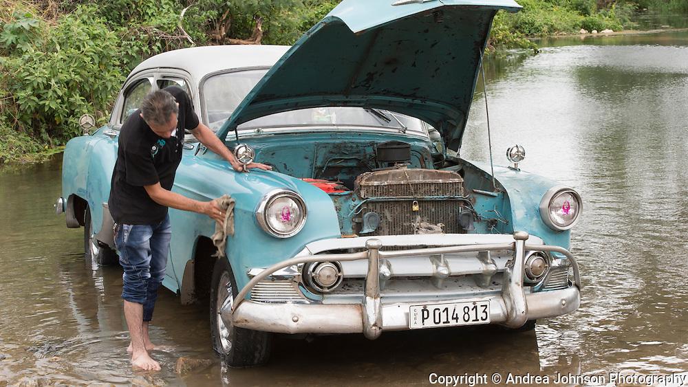 washing classic car by river, Trinidad, Cuba