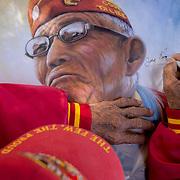 Navajo Code Talker John Kinsel, Sr. signs a poster of himself, July 11, 2019, at his home in Lukachukai, Arizona.