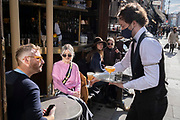 On the day that the UK government eased Covid restrictions to allow non-essential businesses such as shops, pubs, bars, gyms and hairdressers to re-open, customers are served outdoor drinks on Old Compton Street in Soho, on 12th April 2021, in London, England.