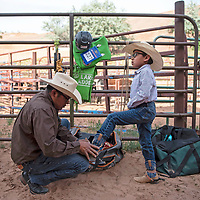 Adrian Lynch crouches down to fasten the bootstraps of his son Anderson Lynch, 8, as he prepares to compete in steer riding Wednesday, June 12 at Red Rock Park during the Gallup Lions Club youth rodeo.
