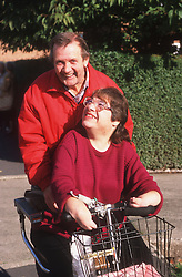 Woman with disability and husband riding electric scooter,