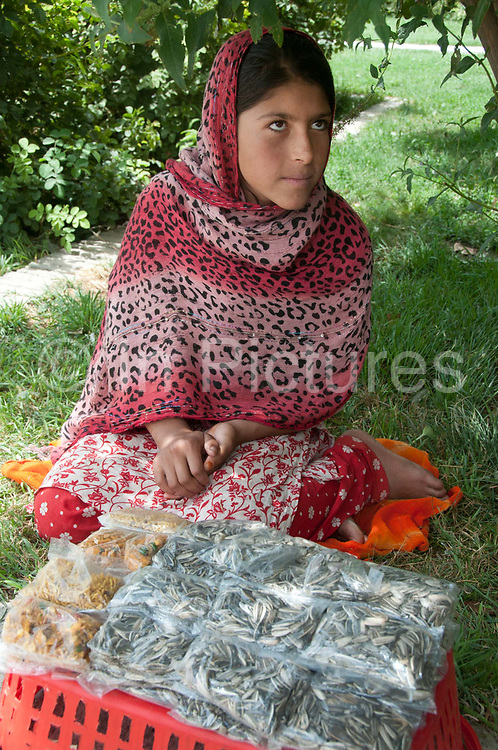 Afghanistan. Kabul. Bagh-e-Babur gardens. Hanifa selling sunflower seeds and bombay mix.