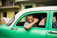 A passenger in the backseat of a vintage car operating as a taxi gives a thumbs-up sign as the taxi navigates a street in the Centro Habana district of Havana, Cuba