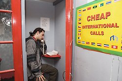Young Czech man in phone booth making a call,