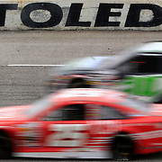 """Two cars drive past the """"Toledo Speedway"""" sign during the Menards 200 ARCA race at Toledo Speedway in Toledo on Sunday, May 20, 2018. THE BLADE/KURT STEISS"""