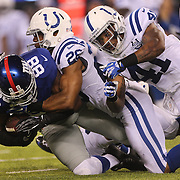 Hakeem Nicks, (left), New York Giants, is tackled by Greg Toler, (centre) and Antoine Bethea, Indianapolis Colts, during the New York Giants V Indianapolis Colts, NFL American Football Pre Season match at MetLife Stadium, East Rutherford, NJ, USA. 18th December 2013. Photo Tim Clayton