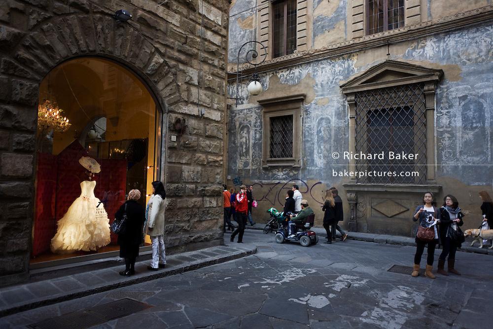 Women admire wedding dress in window of Atelier Aimee bridal shop on Florence's Borgo degli Albizi..