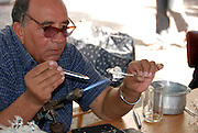 Israel, Tel Aviv, glass artist melting glass on a flame in his outdoor stall