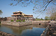 Two men sit under a tree by the moat leading to Ngo Mon Gate with Five Phoenix Watchtower above, Hue Citadel / Imperial City, Hue, Vietnam