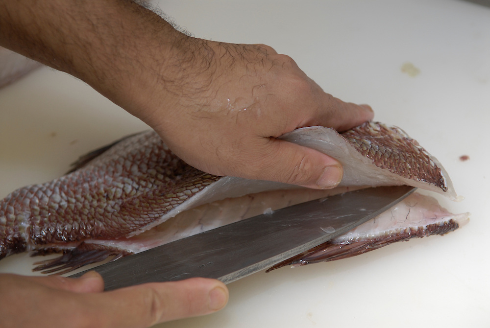 Sakai Shouji, a sushi chef working just a few doors down from the knife shop fillets a fish using one of their knives.