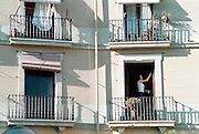 Spanje, Barcelona 10-1-2004..Jonge vrouw wast de ruiten van haar appartement. Frans balkon, ventileren woning, alleenstaand, wonen...Foto: Flip Franssen