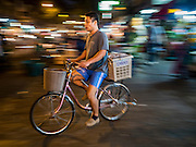 """21 DECEMBER 2015 - BANGKOK, THAILAND:  A man rides his bike past Pak Khlong Talat, also called the Flower Market. The market has been a Bangkok landmark for more than 50 years and is the largest wholesale flower market in Bangkok. A recent renovation resulted in many stalls being closed to make room for chain restaurants to attract tourists. Now Bangkok city officials are threatening to evict sidewalk vendors who line the outside of the market. Evicting the sidewalk vendors is a part of a citywide effort to """"clean up"""" Bangkok.      PHOTO BY JACK KURTZ"""