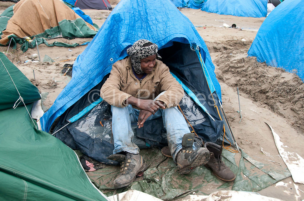 France. Refugees. Calais. So-called Jungle camp . Mohammed, who says he is aged 17, from Darfur, Sudan sits by his tent
