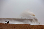 A photographer working as waves crest over Folkstone Harbour Arm as Storm Ciara swept in on February 9th 2020 in Folkestone, United Kingdom. Amber weather warnings were put into place by the MET office as gusts of up to 90mph and heavy rain swept across the UK. An amber warning from the MET office expects a powerful storm that will disrupt air, rail and sea links travel, cancel sports events, cut electrical power and damage property.