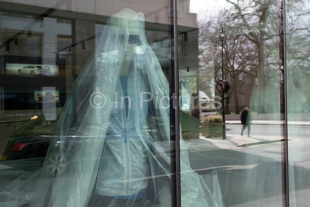 Mannequins are covered in plastic sheeting inside the Porsche showroom in Mayfair as the national coronavirus lockdown three continues on 5th March 2021 in London, United Kingdom. With the roadmap for coming out of the lockdown has been laid out, this nationwide lockdown continues to advise all citizens to follow the message to stay at home, protect the NHS and save lives, and the streets of the capital are quiet and empty of normal numbers of people.