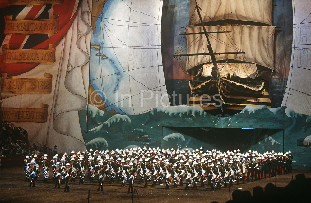 Members of the British Royal Marines band march under a giant backdrop of Lord Horatio Nelson's flagship HMS Victory during the Royal Tournament. Ranks of the musical soldiers appear from between large doors that are already closing behind their last rows. Above them is the huge mural depicting the famous sea battles at which Nelson and his fleet of warship navy were victorious such as Gibraltar; Quiberon; Saintes and Cape St. Vincent. The Royal Tournament was the World's largest military tattoo and pageant, held by the British Armed Forces annually between 1880 and 1999. The venue was originally the Royal Agricultural Hall and latterly the Earls Court Exhibition Centre. In its later years it also acted as a fundraising event for leading forces charities, such as The Royal British Legion.