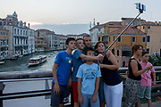 Tourist family take a selfie on Ponte Accademia with the Grand Canal in the background. All looking up into the lens of their phone, the family members consisting of the parents and their children stand on this major bridge crossing the canal where a Vaporetto ferry is about to pass underneath. Vendors sell selfie sticks everywhere on the streets and the selfie remains a firm favourite way of recording the family holiday.