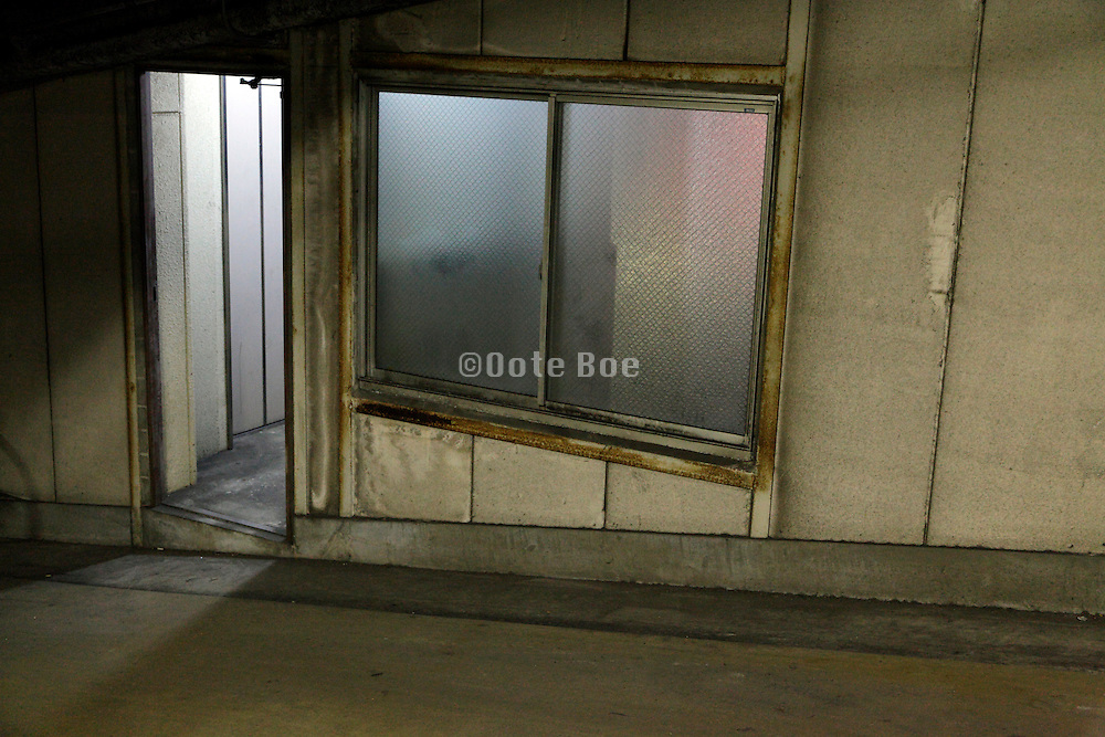 door to elevator and window in a parking garage at night