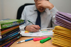 Embargoed to 0001 Thursday August 30 File photo dated 05/03/17 of a teacher next to a pile of classroom books. Salary supplements such as bonuses should be given to teachers in shortage subjects to help deal with a growing recruitment and retention crisis, according to a report.