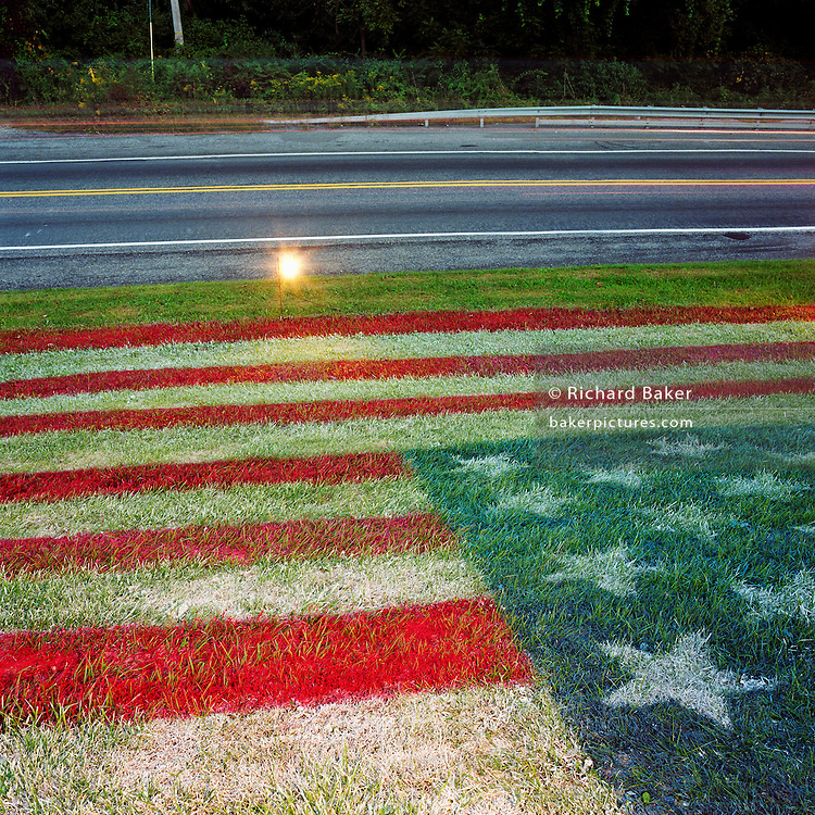 During a journey into America's hinterlands, days after the September 11th attacks in New York and Washington DC, an American flag has been sprayed with aerosol paint on a grassy knoll by a local garage owner near Sinking Spring, Pennsylvania. In outpourings of grief, anger and patriotic rhetoric, flags were flown as never before as  America sought to express their emotions and a unity. A spotlight shines across the bank to show passing motorists the creative stars and stripes artwork on the roadside. Sinking Spring's Native American tribe in this were known as the Minsi or Wolf tribe who had the reputation for being quite warlike at times..