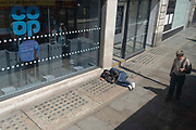 A wealthier man looks down at a male lying on the pavement outside a branch of the Co-Op bank on the Strand, on 23rd June 2021, in Westminster, London, England.