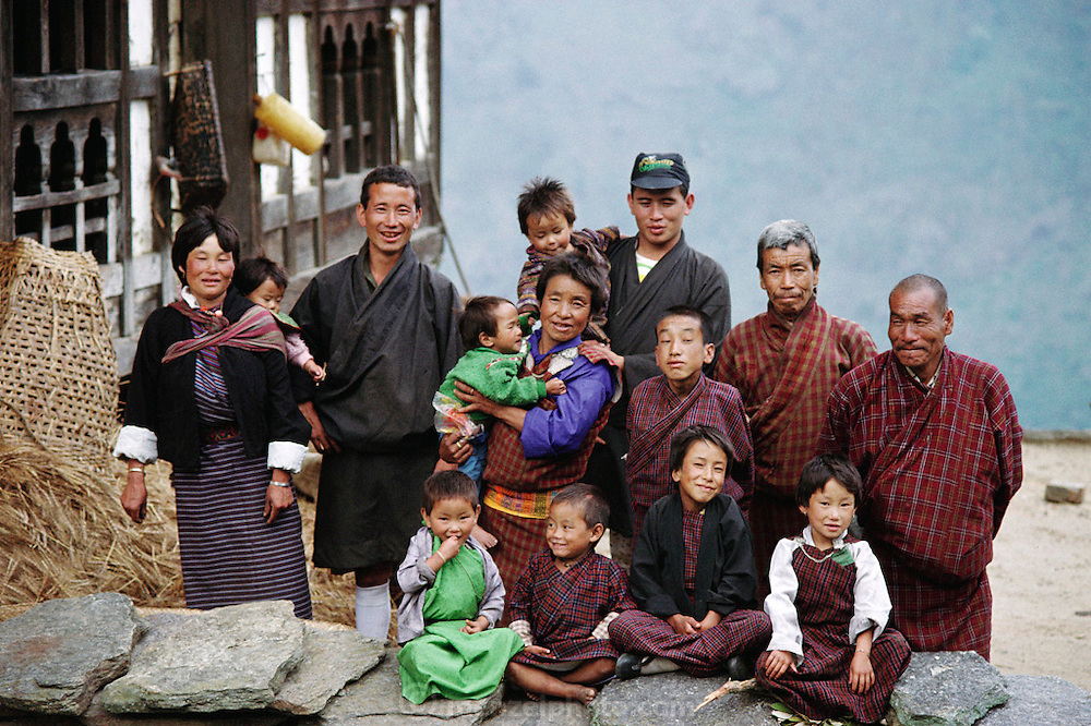 Nalim and Namgay family portrait outside their home in Shingkhey, Bhutan. The family of subsistence farmers lives in a 3-story rammed-earth house in the hillside village of Shingkhey, Bhutan. Namgay, who has a hunched back and a clubfoot, grinds grain for neighbors with a small mill his family purchased from the government. They are paying for the mill as they can (often the payment is made in grain and mustard oil). Namgay is also a reader of sacred texts and conducts house cleansing and healing ceremonies for their 14-house village. From Peter Menzel's Material World Project that showed 30 statistically average families in 30 countries with all their possessions.