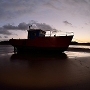 """Little red boat blue with a little light in the window.<br /> <br /> Barmouth (Welsh: Abermaw (formal); Y Bermo (colloquial)) is a town in the county of Gwynedd, north-western Wales, lying on the estuary of the River Mawddach and Cardigan Bay. Historically in Merionethshire, the English form of the name is derived from """"Aber"""" (estuary) and the river's name """"Mawddach""""<br /> <br /> The town is served by Barmouth railway station.<br /> <br /> The town grew around the shipbuilding industry, and more recently as a seaside resort. Notable buildings include the mediaeval Tŷ Gwyn tower house, the 19th century Tŷ Crwn roundhouse prison and St John's Church.<br /> <br /> William Wordsworth, a visitor to Barmouth in the 19th century, described it thus: """"With a fine sea view in front, the mountains behind, the glorious estuary running eight miles inland, and Cadair Idris within compass of a day's walk, Barmouth can always hold its own against any rival.""""[this quote needs a citation]<br /> <br /> There is also a new Lifeboat Visitors' Centre, where visitors can purchase souvenirs, and take a look at the RNLI lifeboat from the viewing gallery. The busy harbour plays host to the annual Three Peaks yacht race.<br /> <br /> Barmouth Bridge, which takes the Cambrian Line over the River Mawddach, was also formerly at the end of the GWR Ruabon Barmouth line, which passed through Bala and Dolgellau. The southern end of the bridge is now the start of the Mawddach Trail, a cycle path and walk way that utilises the old trackbed.<br /> <br /> The Barmouth Ferry sails from Barmouth to Penrhyn Point, where it connects with the narrow gauge Fairbourne Railway for the village of Fairbourne.<br /> <br /> Barmouth is (geographically) one of the closest seaside resorts to the English West Midlands and a large proportion of its tourist visitors, as well as its permanent residents, are from Wolverhampton, Birmingham, Dudley and other parts of the Black Country, and Telford, Shropshire."""